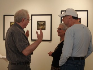 Dan Burkholder describes his working methods to some gallery visitors. One of his images is on the wall.